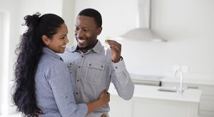 Couple hugging and holding keys in new home